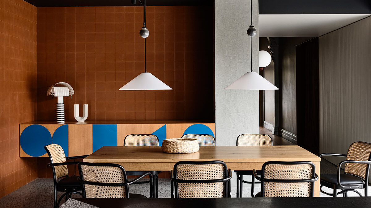 Two pendant lights centred above an oak dining table with a backdrop of terra cotta tiled walls and a corridor.