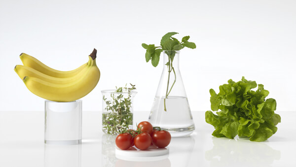 Fresh Fruit and Vegetables on a White Countertop in Glass Beakers