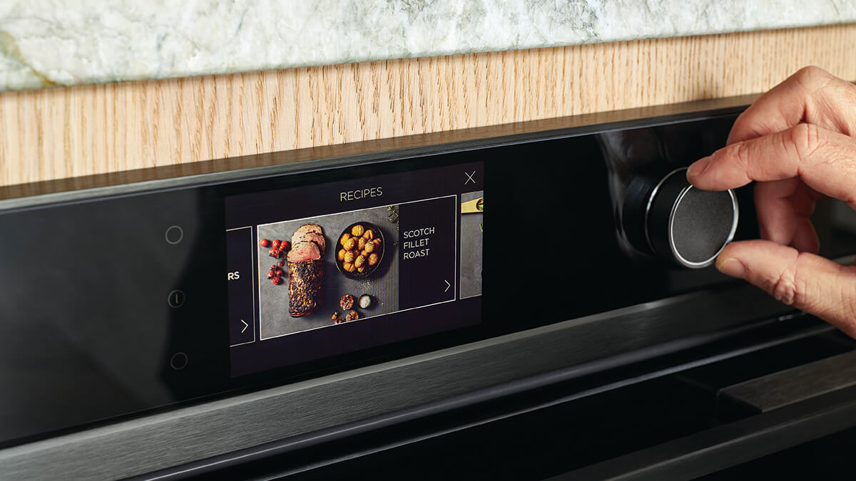Close up of hand spinning dial of the touchscreen oven.