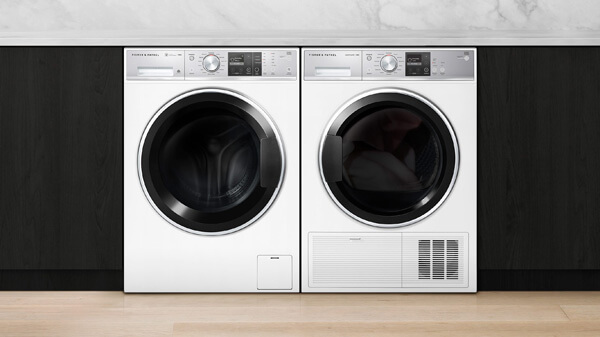 White Washing Machine & Dryer arranged Side-by-Side and set in Black Cabinetry