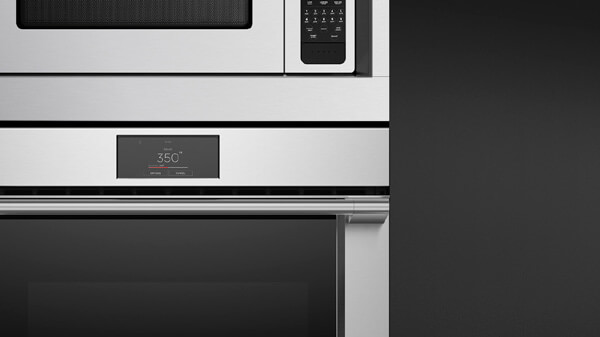 Front View of a Stainless Steel Professional Style Microwave Oven atop a Matching Oven Seamlessly Framed by a Trim Kit.