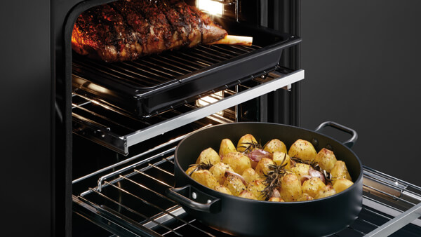 Open Multi Shelved Oven with a Tray of Lamb and Roasted Potatoes.