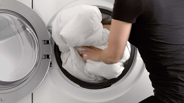 Woman Loading a Thick Duvet Into Washing Machine.